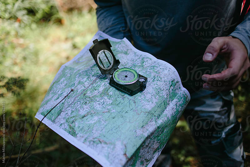 Man orienteering with the compass and map by Marko Milovanović for Stocksy United