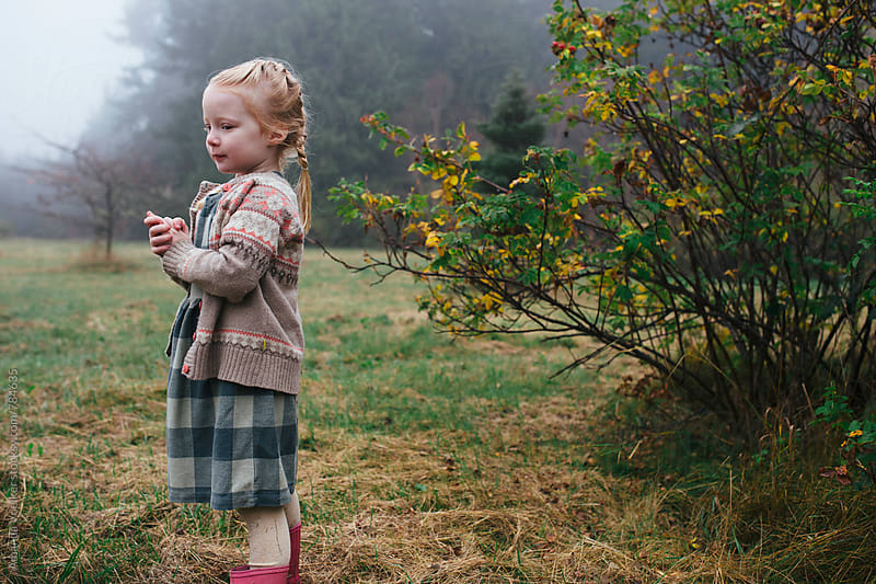 A Little Girl Tries to warm her hands on a chilly fall morning by Amanda Voelker for Stocksy United