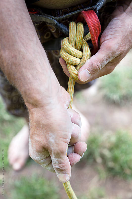 Free climber tying bowline knot before a climb  by Jovana Milanko for Stocksy United