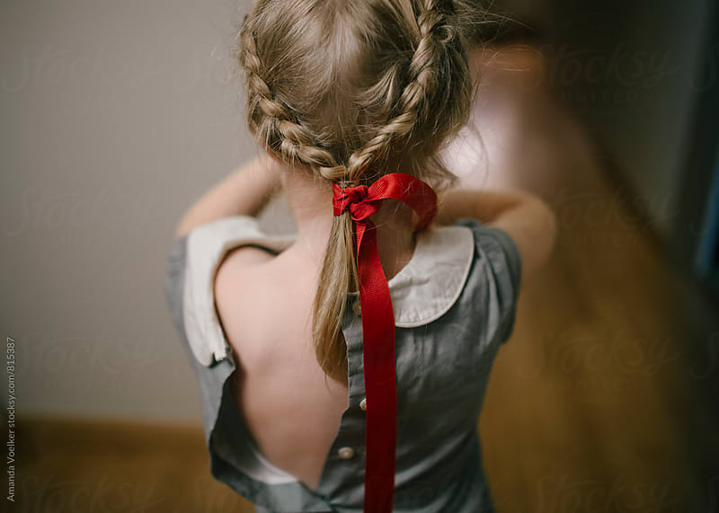 Little Girl With Red Ribbon in Her Braided Hair and Dress Back Unbuttoned by Amanda Voelker for Stocksy United