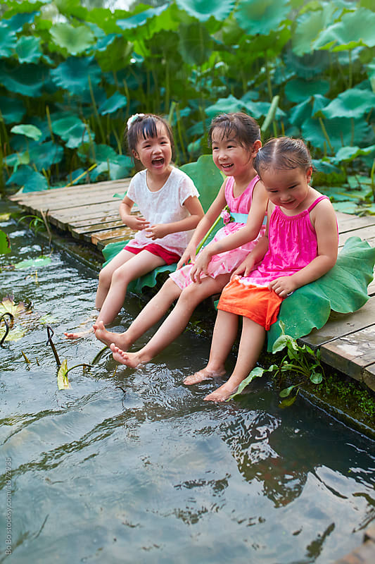 three little asian or CHinese girl playing water by the pond side by cuiyan Liu for Stocksy United