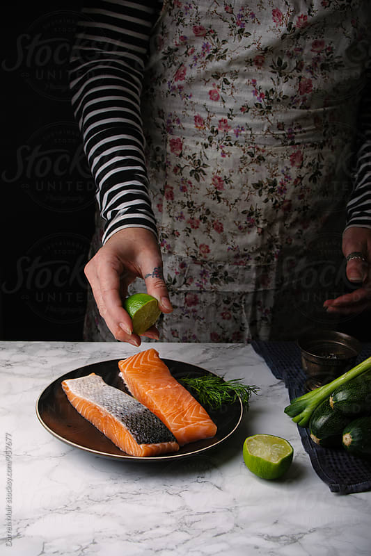 Woman preparing a salmon meal:Woman squeezing lime juice on salmon fillets. by Darren Muir for Stocksy United