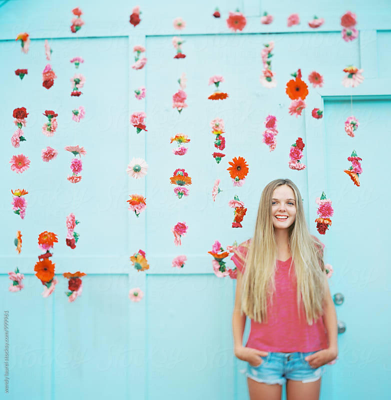 girl in pink shirt against blue wall with pink hanging flowers by wendy laurel for Stocksy United