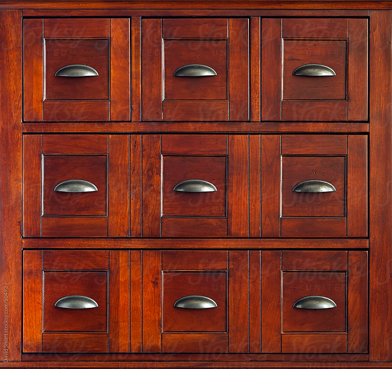 Closed drawers of an apothecary chest that is made of rich, dark wood by David Smart for Stocksy United