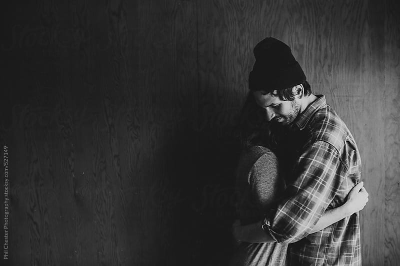 Black and white of couple hugging each other by Phil Chester Photography for Stocksy United