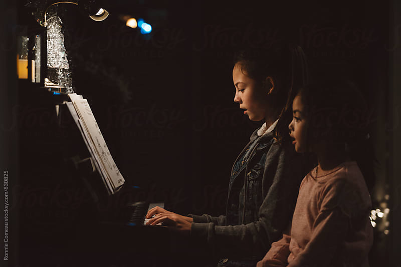 Sisters Perform Piano Duet by Ronnie Comeau for Stocksy United