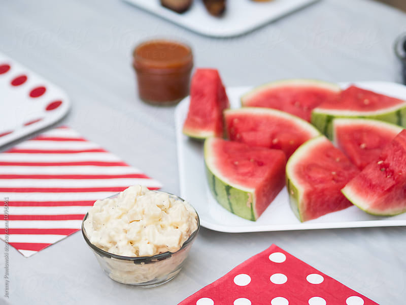 Potato salad and watermelon on table for bbq by Jeremy Pawlowski for Stocksy United