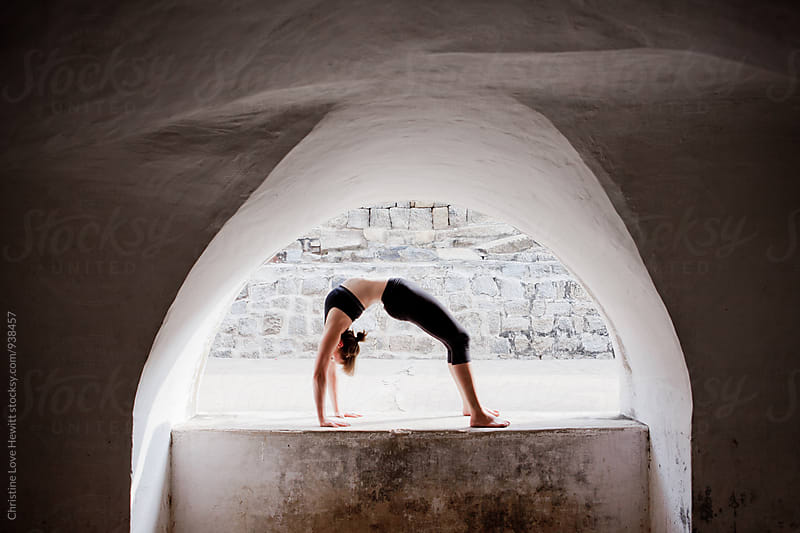 Woman doing yoga in an archway by Christine Love Hewitt for Stocksy United