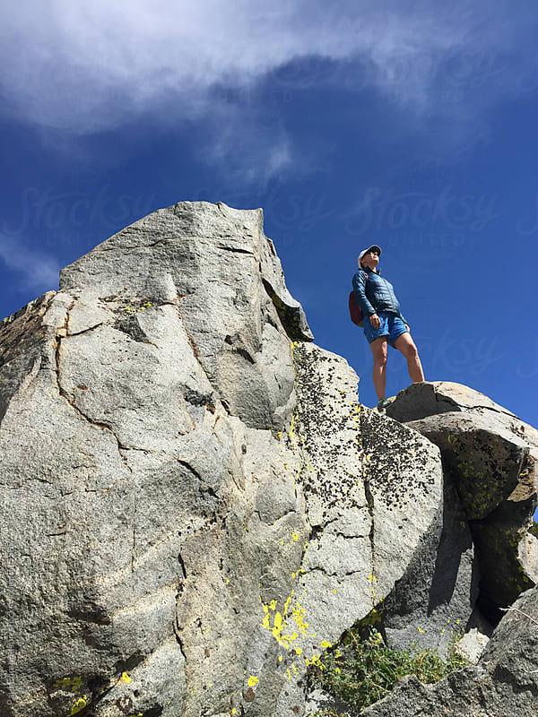 Female hiker standing on rocky mountain summit by Paul Edmondson for Stocksy United