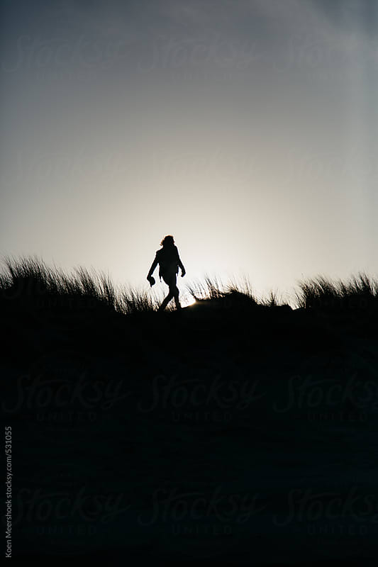 Silhouette of a hip young man walking through some dunes. by Koen Meershoek for Stocksy United