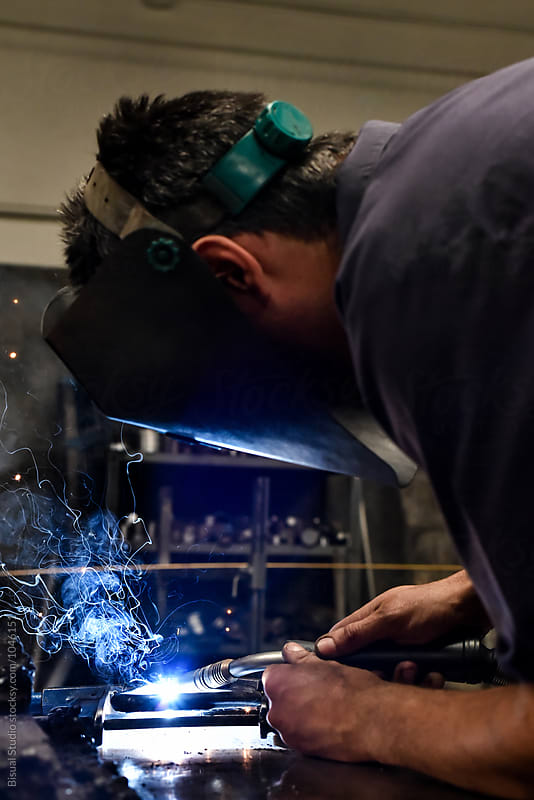 Welder in a workshop by Bisual Studio for Stocksy United