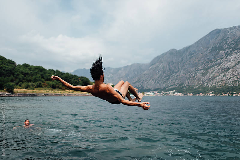 Young man jumping in water by Boris Jovanovic for Stocksy United
