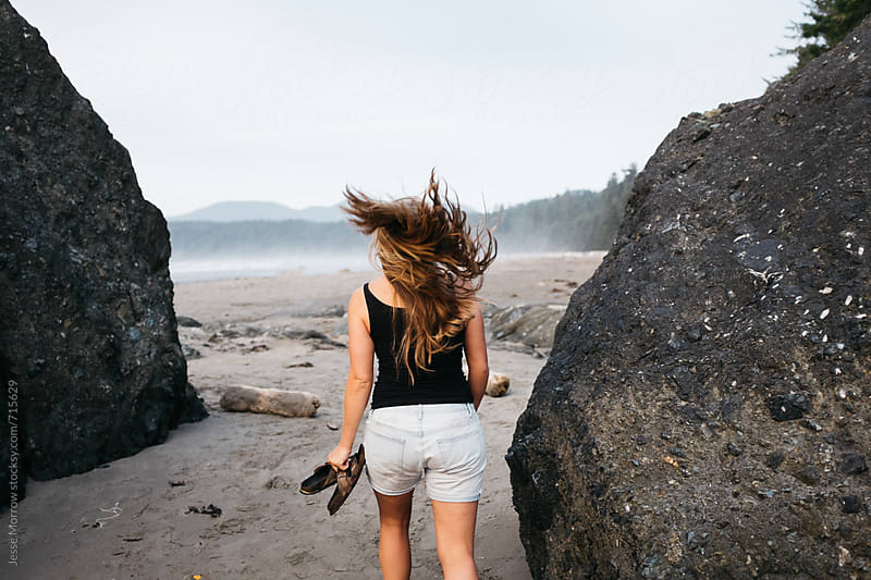 young female flipping hair on beach  by Jesse Morrow for Stocksy United