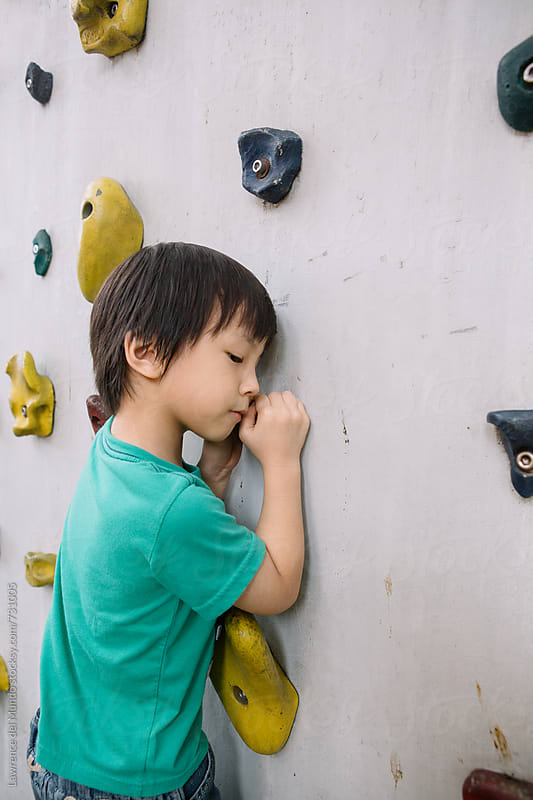 A very determined young kid working the rock climbing wall  by Lawrence del Mundo for Stocksy United