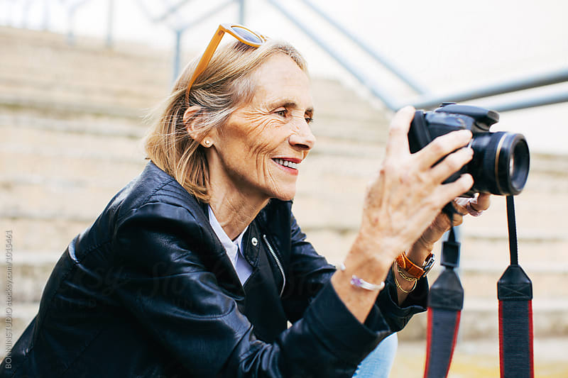 Retired woman taking photos of the city. by BONNINSTUDIO for Stocksy United