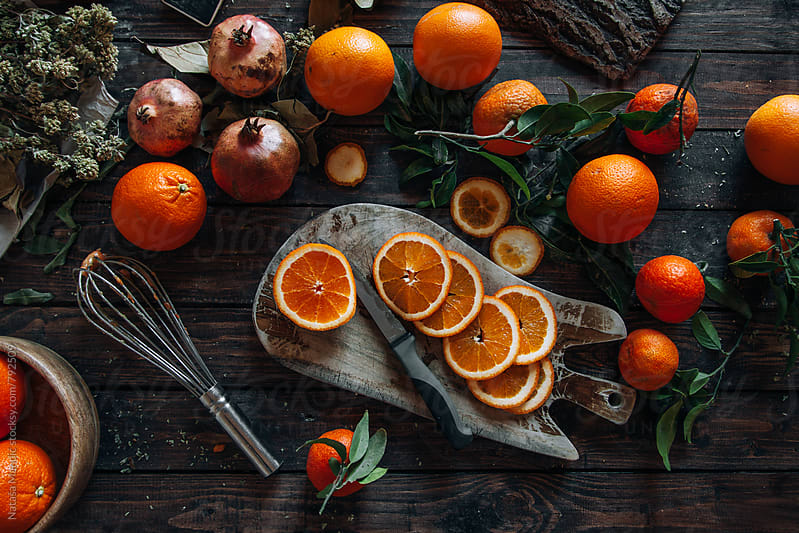 Oranges on a wooden dark table by Nataša Mandić for Stocksy United