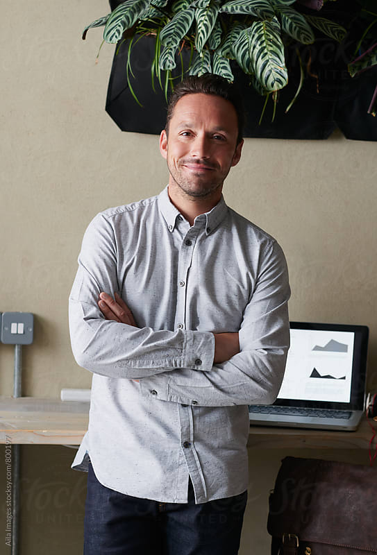 Handsome young businessman smiling friendly eyes waering smart grey shirt relaxing in cafe using wireless connection in cafe by Aila Images for Stocksy United