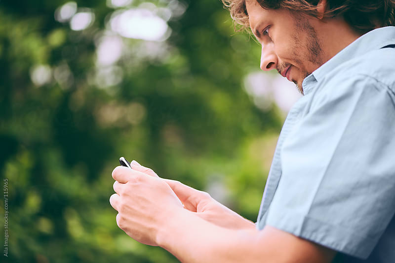 Cute Guy using mobile device by Aila Images for Stocksy United