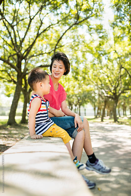 Woman and her son sitting on concrete parapet in park by Lawren Lu for Stocksy United
