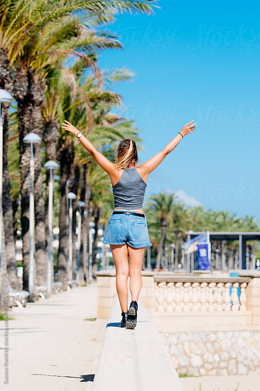 Cheerful woman doing balance on the promenade by Susana Ramírez for Stocksy United