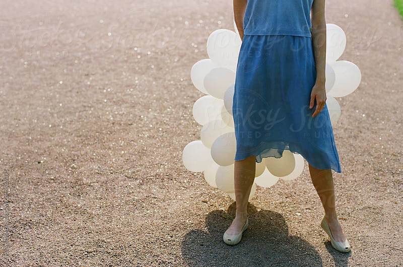 Woman with white balloons by Liubov Burakova for Stocksy United
