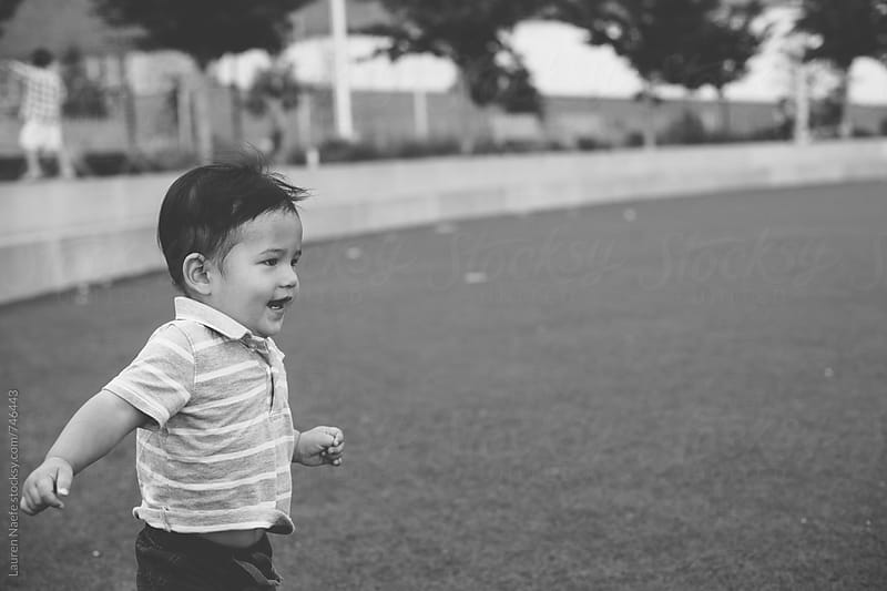 Toddler running in the park by Lauren Naefe for Stocksy United