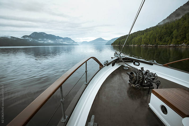 A boat travels through the coastal fjords of British Columbia's Great Bear Rainforest. by Robert Zaleski for Stocksy United