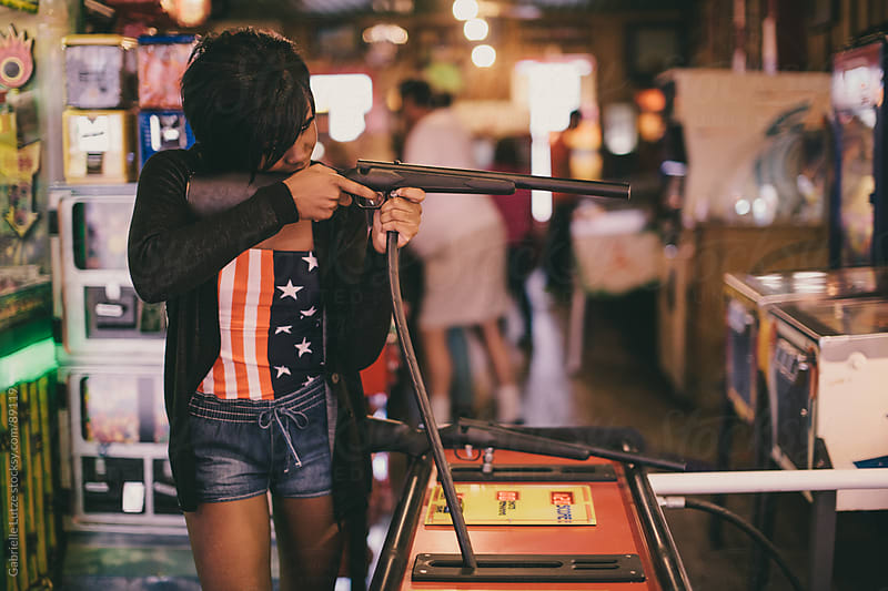 Black girl Playing a rifle game at an arcade by Gabrielle Lutze for Stocksy United