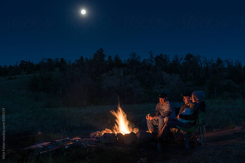 Friends and family by campfire with full moon by Mick Follari for Stocksy United