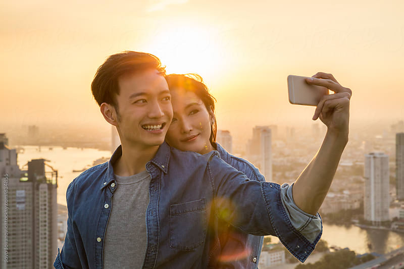 Smiling young couple taking a selfie at sunset by Jovo Jovanovic for Stocksy United