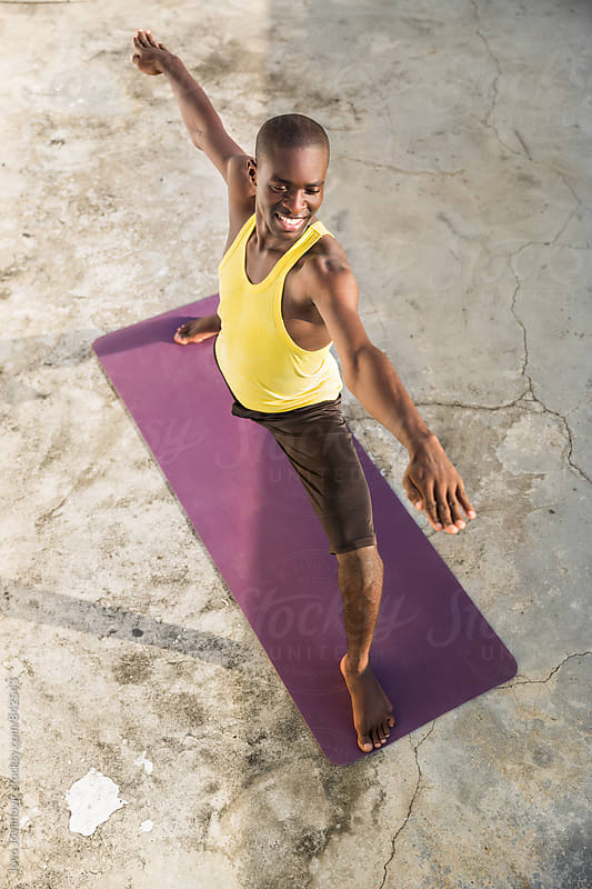 Smiling young man extending his arms while practicing yoga by Jovo Jovanovic for Stocksy United