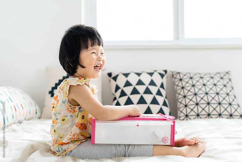 Adorable girl playing with toys on bed by MaaHoo Studio for Stocksy United