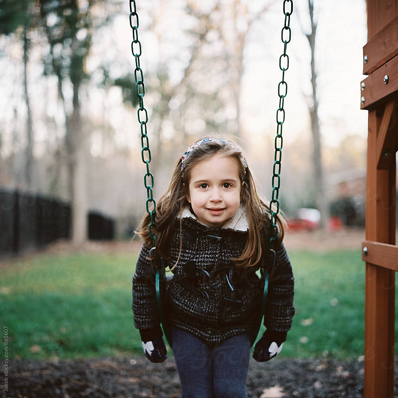 Beautiful young girl in a coat sitting on a swing by Jakob for Stocksy United
