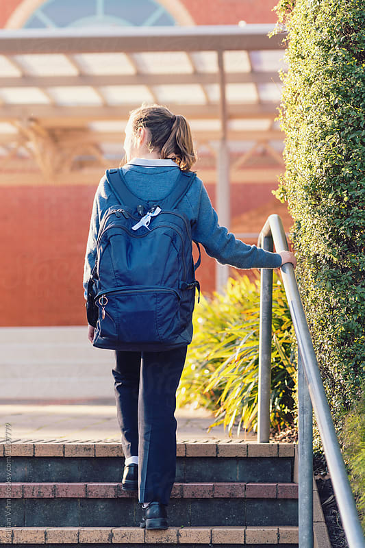 australian high school student with large backpack walking up steps at school