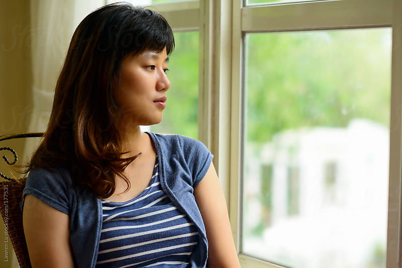 Woman looking out beside window by Lawren Lu for Stocksy United