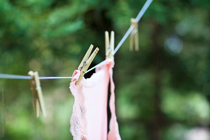 Woman's lacy tank top drying on the clothes line outside by Carolyn Lagattuta for Stocksy United