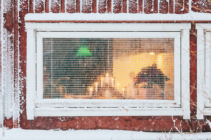 Scandinavian candles in a frozen window at Christmas by Lior + Lone for Stocksy United