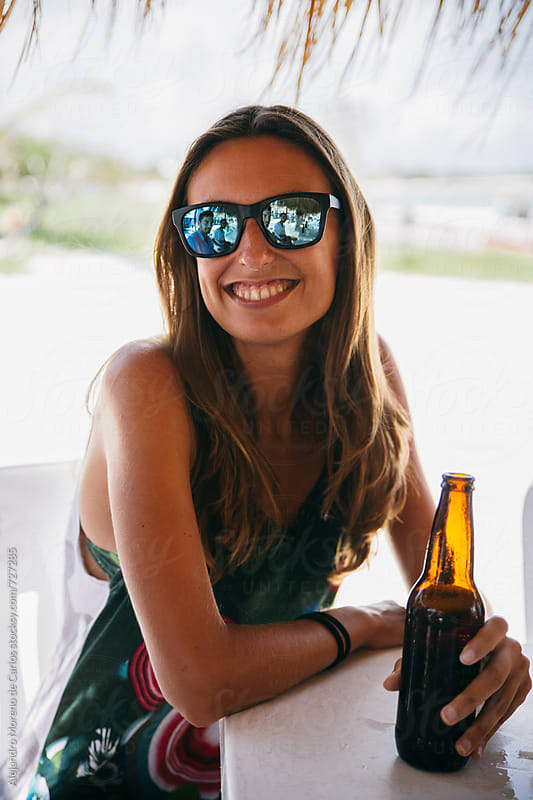Young smiling woman with a beer bottle in a beach bar by Alejandro Moreno de Carlos for Stocksy United