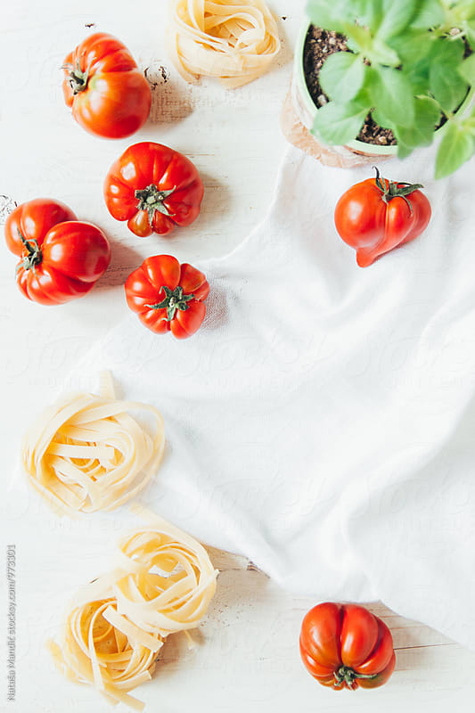 Fresh tomatoes, basil and tagliatelle ready to be cooked by Nataša Mandić for Stocksy United