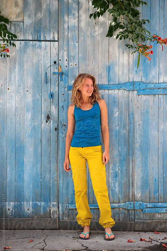 Woman in colorful clothing standing in front of a blue door outside by RG&B Images for Stocksy United