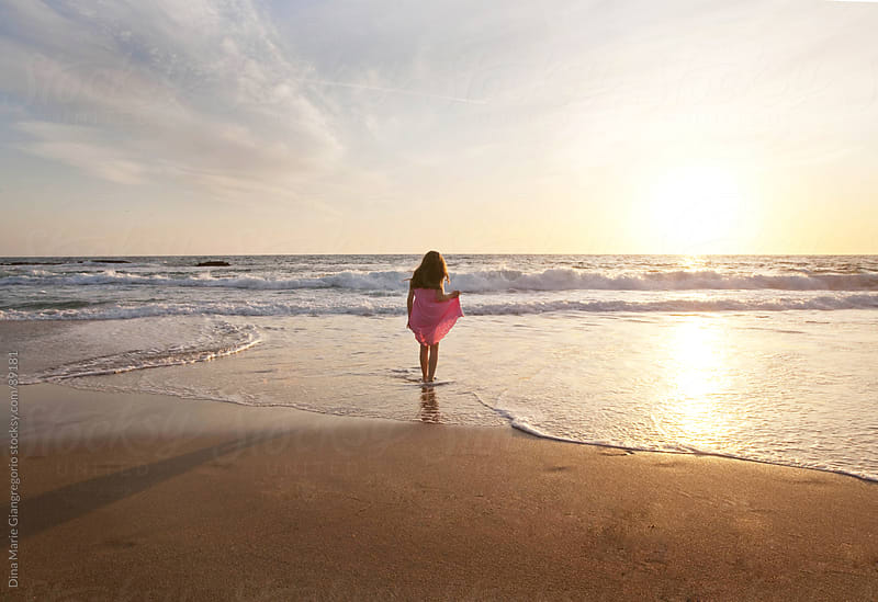 Wide angle view of girl at beach holding dress up by Dina Giangregorio for Stocksy United