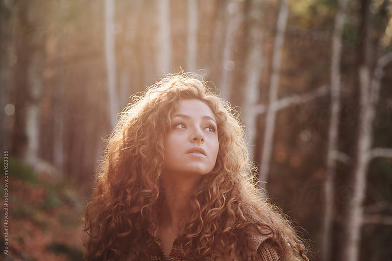 Young woman looking around in the forest by Aleksandar Novoselski for Stocksy United