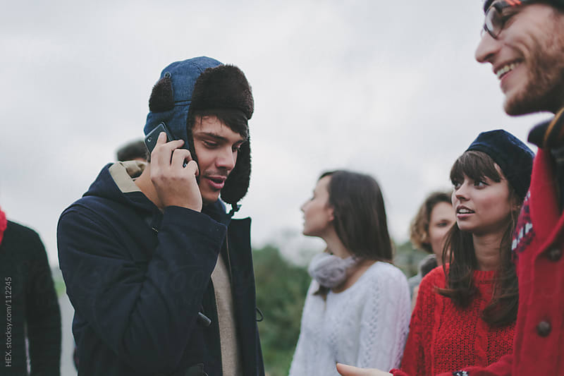 Young Man on the Phone With Friends by HEX. for Stocksy United