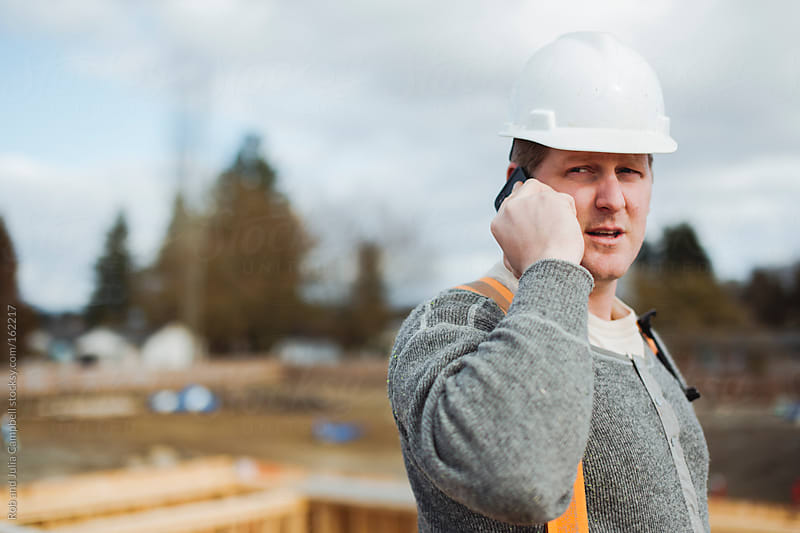 Carpenter man talking on cell phone at construction site by Rob and Julia Campbell for Stocksy United