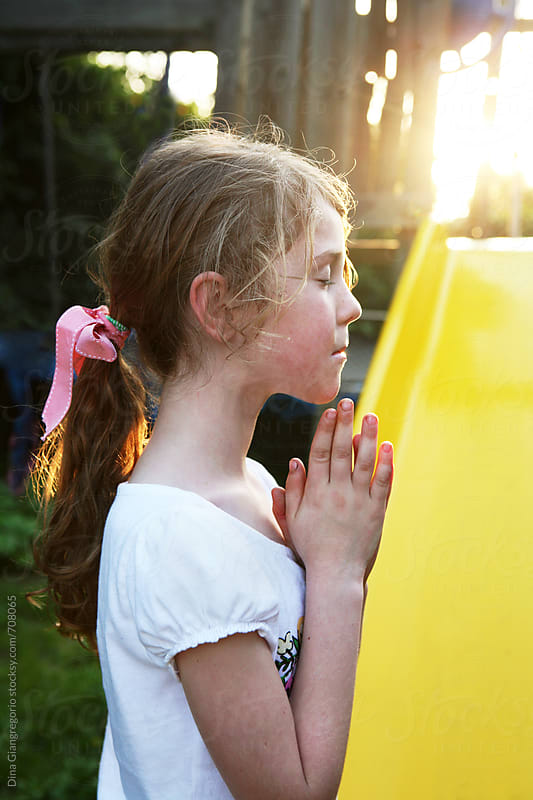 Girl Next To Slide With Hands In Prayer Position by Dina Giangregorio for Stocksy United