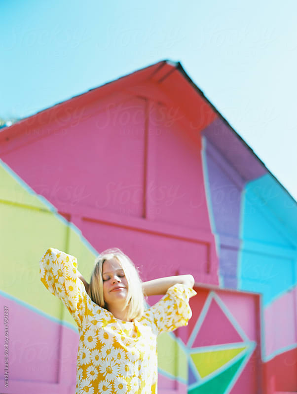 blonde teen with yellow floral dress in front of colorful mural by wendy laurel for Stocksy United