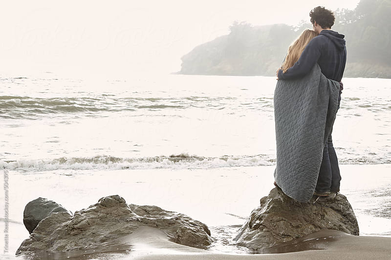 Couple embracing on rock at beach in California  by Trinette Reed for Stocksy United