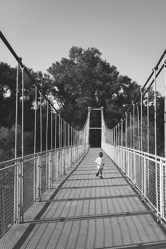 Boy running trough bridge. by Dejan Ristovski for Stocksy United