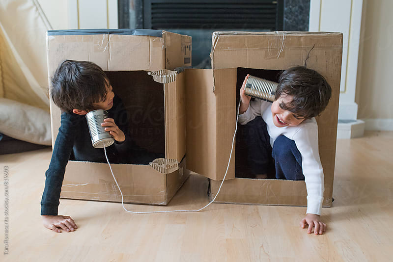 two brothers laughing while playing with a tin can telephone by Tara Romasanta for Stocksy United