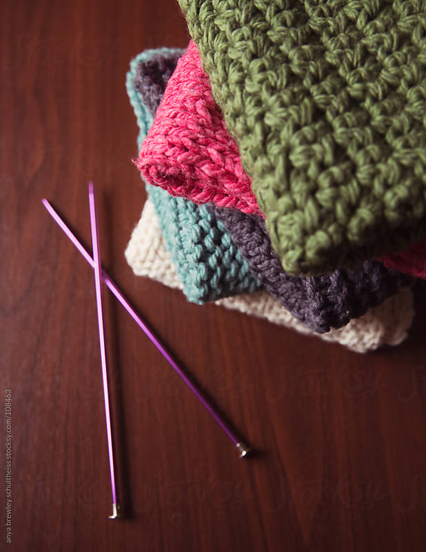 Pile of knitted blankets with a pair of knitting needles by anya brewley schultheiss for Stocksy United